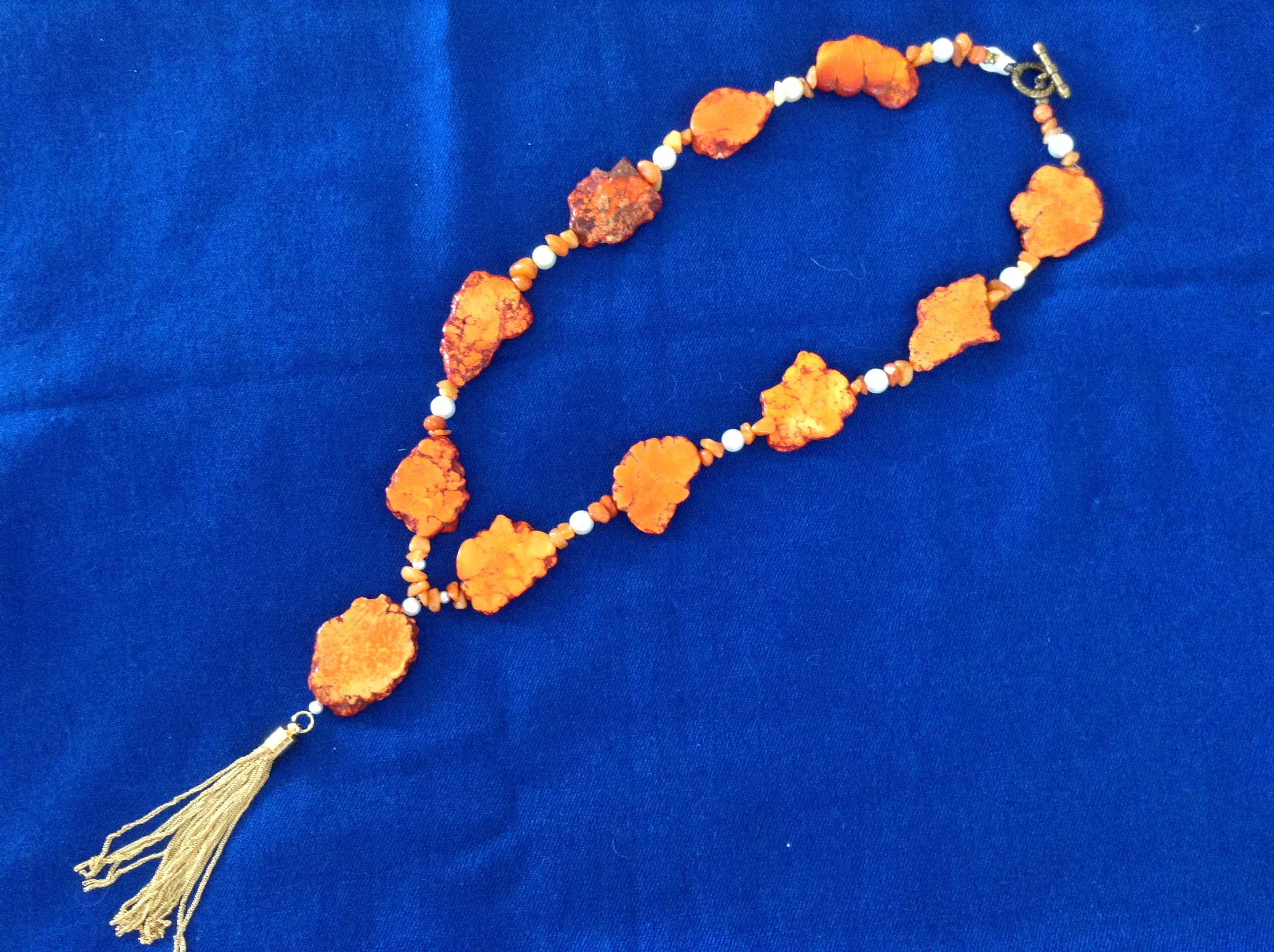 Orange stenhalsband med tofs